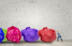 Construction man pushing big crumpled balls of colorful paper as creativity sign